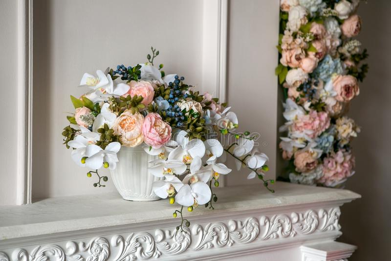 Un bouquet des pivoines, des orchidées et des myrtilles dans un pot de fleurs blanc sur une cheminée blanche dans un style classi photographie stock libre de droits