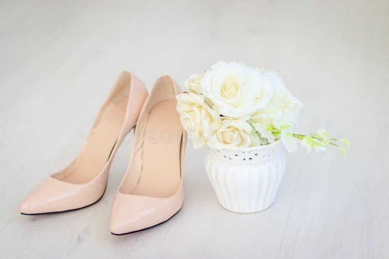 Un bouquet des roses blanches dans un vase et des chaussures Préparations de mariage images libres de droits