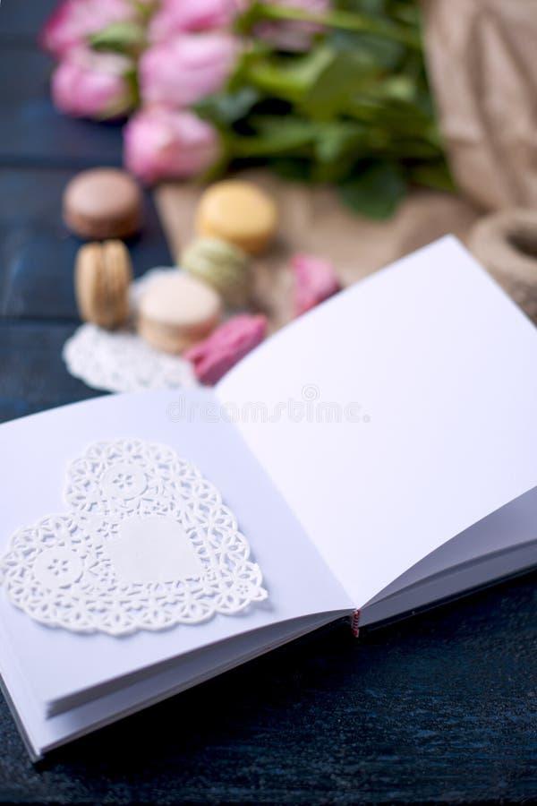 Un bouquet des roses est rose, au papier gris et à un coeur blanc Ouvrez le cahier Une glace de vin rouge Macarons doux de pâtes  photo stock