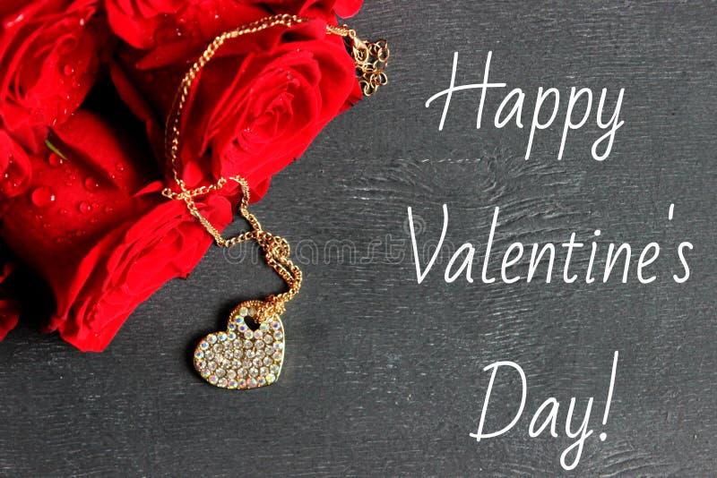 Un bouquet des roses rouges et d'un médaillon d'or sous forme de coeur sur un fond noir en bois photos libres de droits