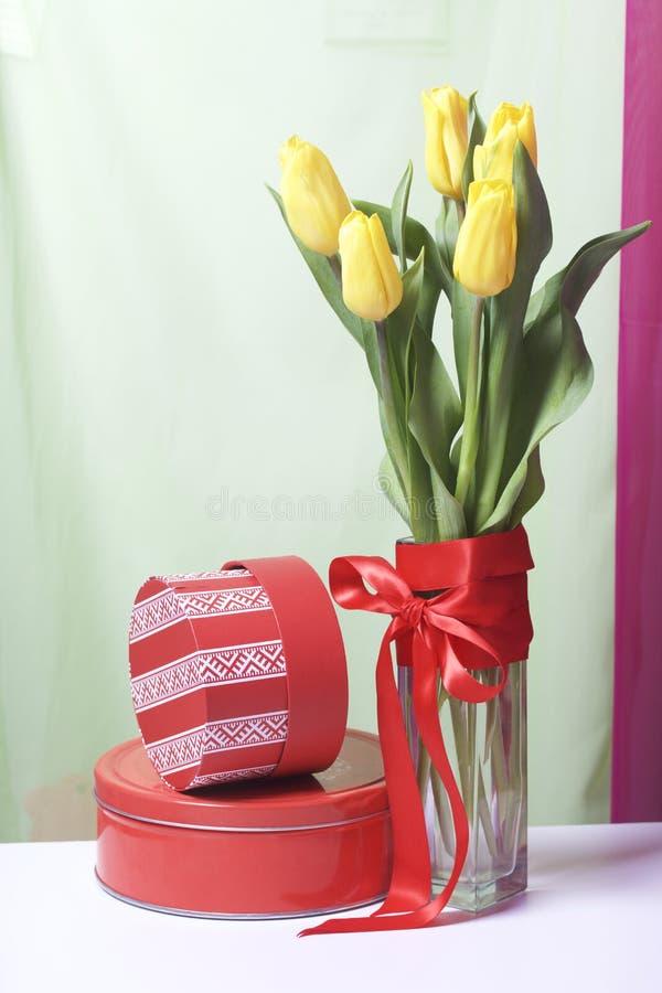 Un bouquet des tulipes jaunes se tient dans un vase en verre enveloppé dans un ruban rouge attaché à un arc Tout près il y a des  photographie stock