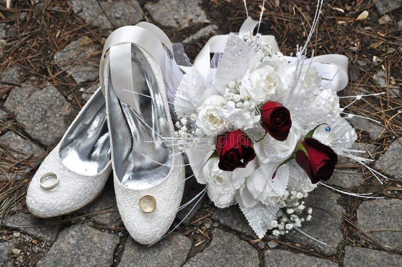 Un bouquet, une chaussure et des anneaux nuptiales de luxe images stock