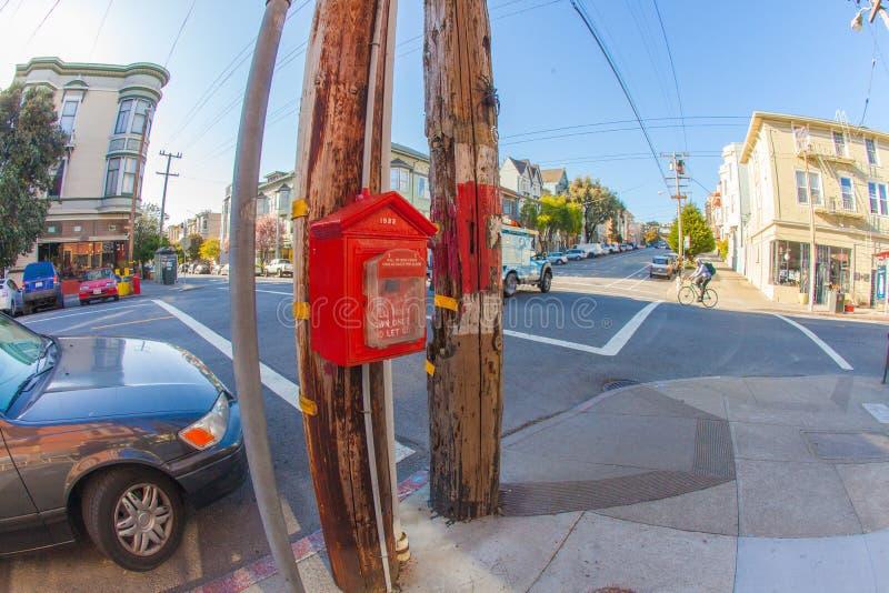 Un bouton d'alarme de bouche d'incendie dans les agains rouges un poteau en bois à une calorie image libre de droits