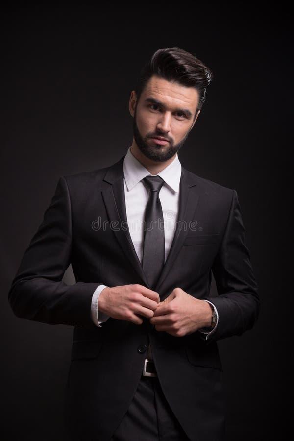Un boutonnage de regard sérieux de costume d'appareil-photo de jeune homme photos stock
