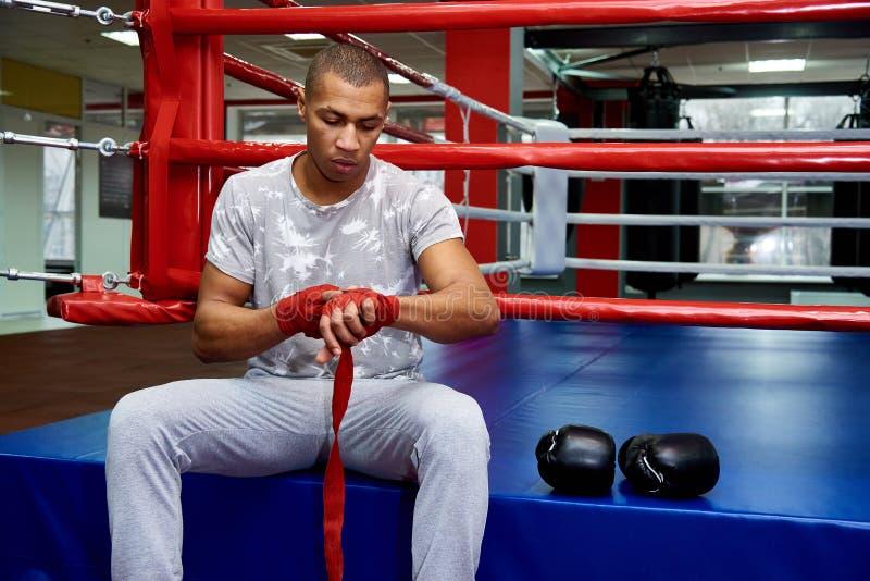 Un boxeador con los vendajes en sus brazos se sienta en el anillo con los guantes de boxeo foto de archivo