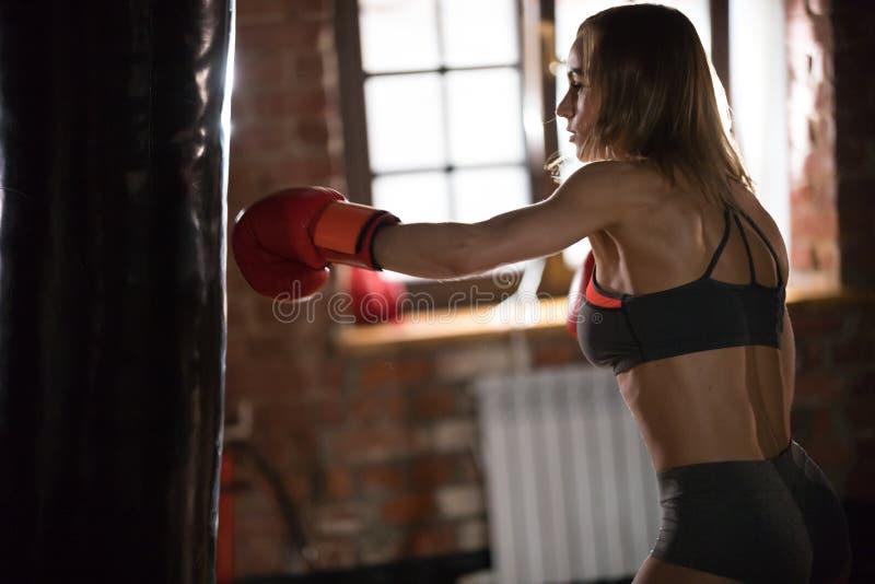 Un boxeador de la mujer que golpea el saco de arena en el gimnasio en el entrenamiento foto de archivo