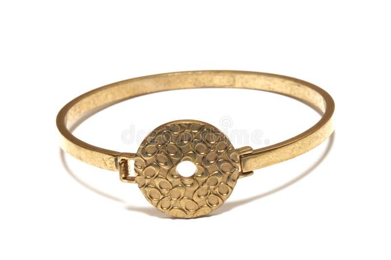 Un braccialetto dorato del braccialetto del bronzo dell'ottone con un disco modellato fotografia stock