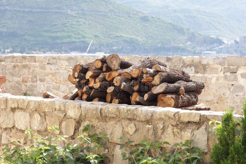 Un'bracciata di legna da ardere su uno scaffale di pietra un giorno soleggiato in mezzo delle montagne immagini stock
