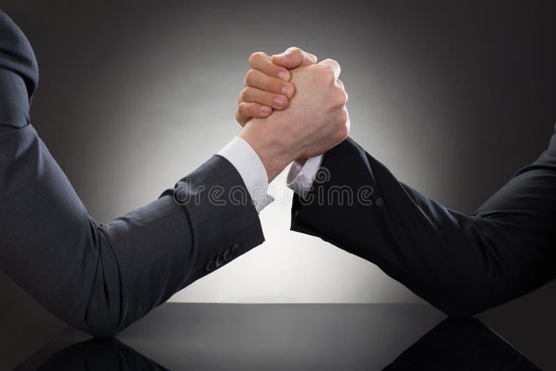 Un braccio di ferro di due uomini d'affari immagine stock