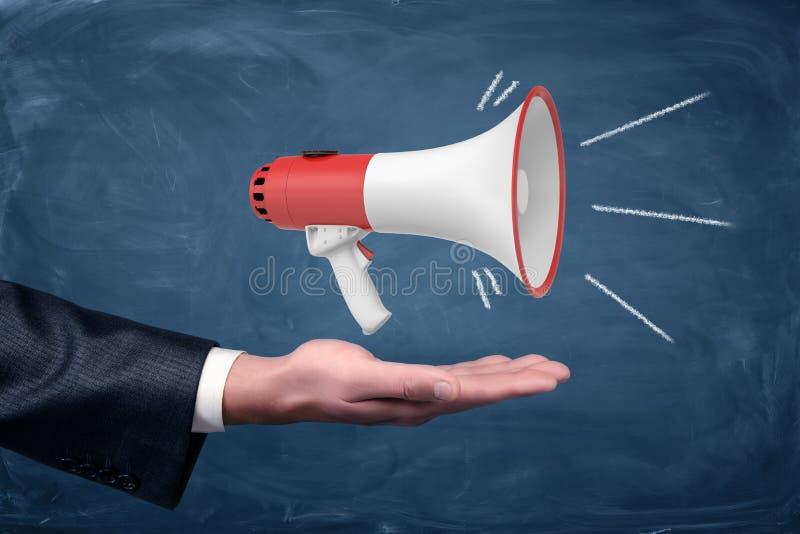 Un bras du ` s d'homme d'affaires avec une paume tenue dans la main haute et un chantier du mégaphone blanc et rouge se tenant là image libre de droits