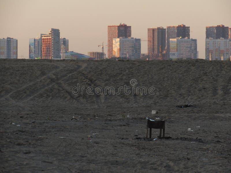 Un brasero negro solo en la arena gris de una playa con las casas de ciudad cuadradas distantes en el amanecer imagenes de archivo