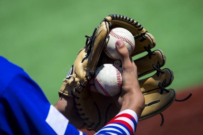 Un brazo estira hacia fuera para coger un béisbol usando un gl de cuero gastado fotos de archivo libres de regalías