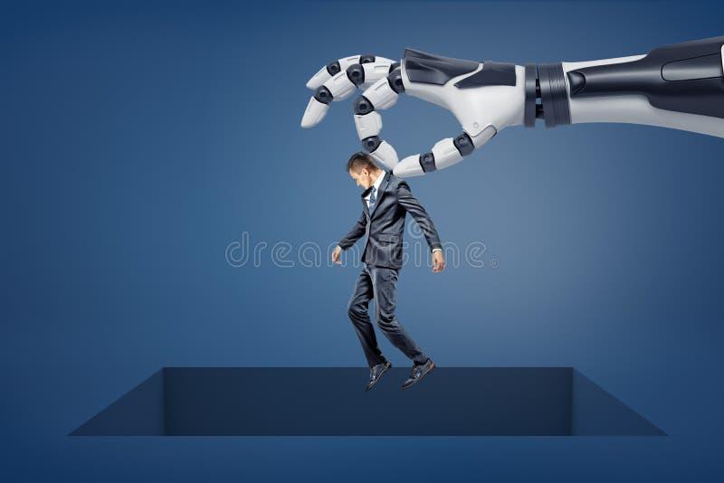 Un brazo robótico gigante detiene a un pequeño hombre de negocios sobre una abertura vacía cuadrada grande en el piso imágenes de archivo libres de regalías