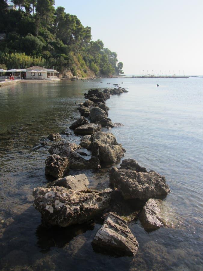 Un brise-lames en pierre massif crée une principale ligne vers s'étendre Les eaux calmes reflètent des cieux gris et une palette  photo libre de droits