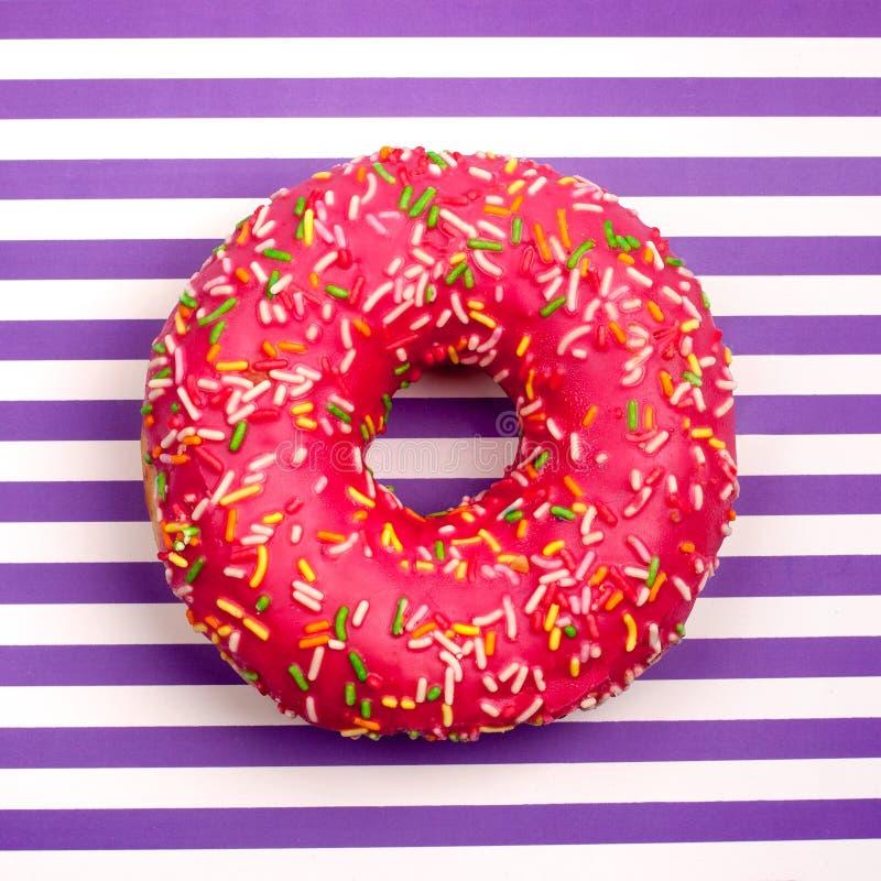 Un buñuelo rosado de la fruta en cierre púrpura y blanco rayado de la opinión superior del fondo de las rayas para arriba foto de archivo