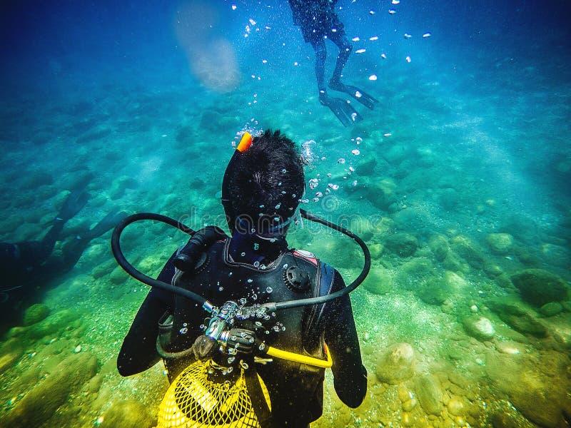 Un buceador de nuevo a la cámara, mirando a otro buceador en el mar imagenes de archivo