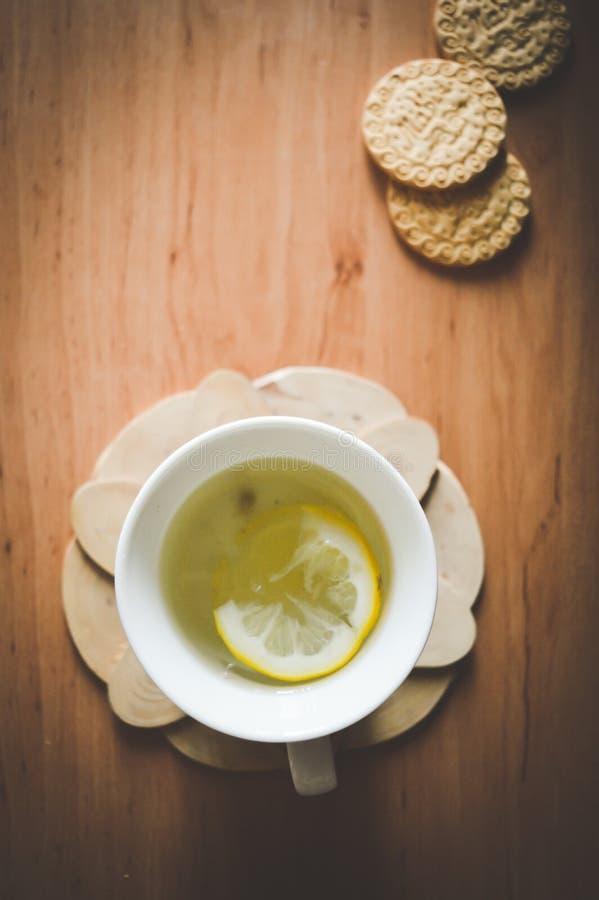 Un buen té con las hierbas y las galletas en la cocina fotos de archivo