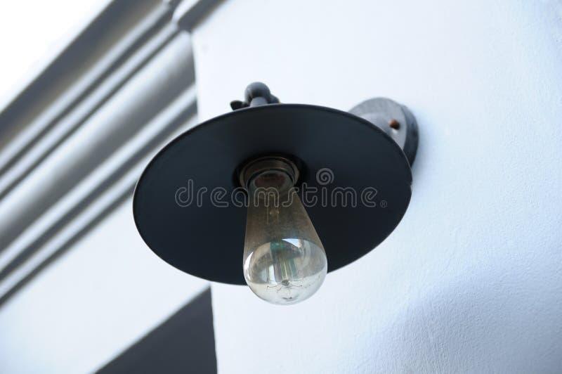 Un bulbo de lámpara abierto por una pared del borde de la carretera fotos de archivo