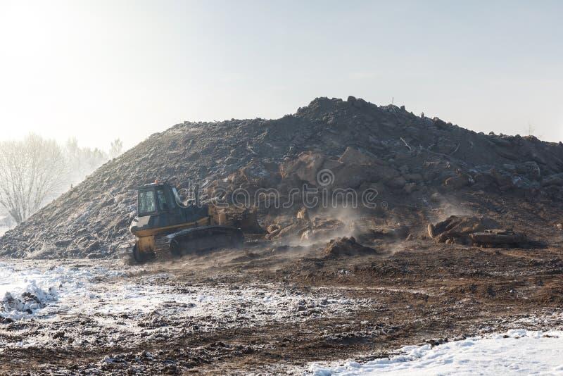 Un bulldozer che funziona nel giorno di inverno fotografia stock