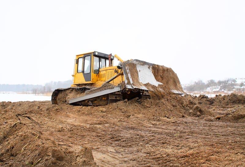 Un bulldozer giallo che funziona in inverno immagine stock