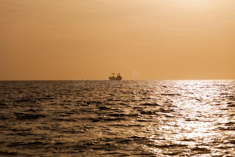 Un buque de carga en el mar en la puesta del sol 1 imagen de archivo libre de regalías