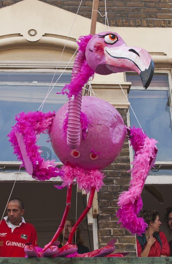 Un burattino gigante del fenicottero che pende da un appartamento immagine stock