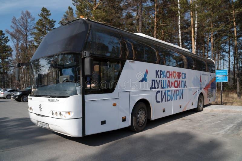 """Un bus di giro a due piani con l'iscrizione """"Krasnojarsk - l'anima ed il potere della Siberia """"sta sui turisti aspettanti dell'au immagine stock libera da diritti"""