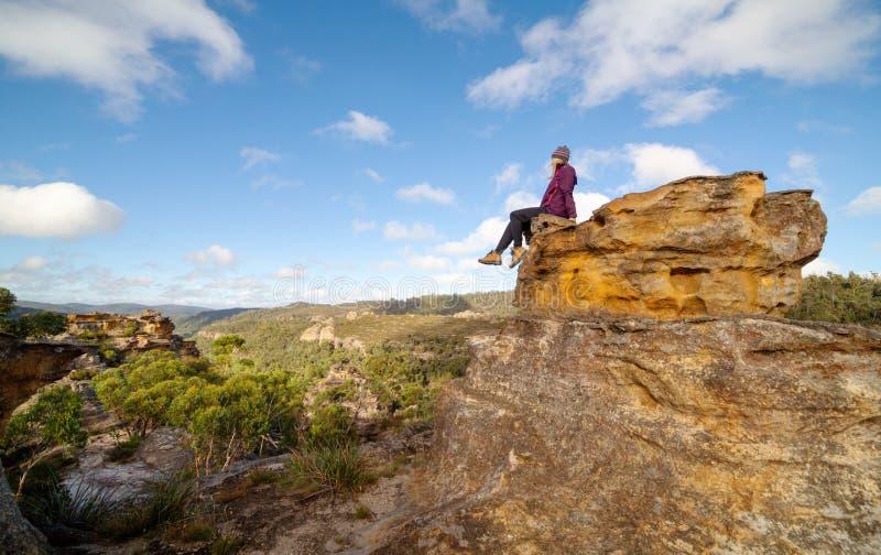 Un bushwalker se repose haut placé sur un paysage des pagodas, des vallées, des caniveaux et des canyons photo libre de droits