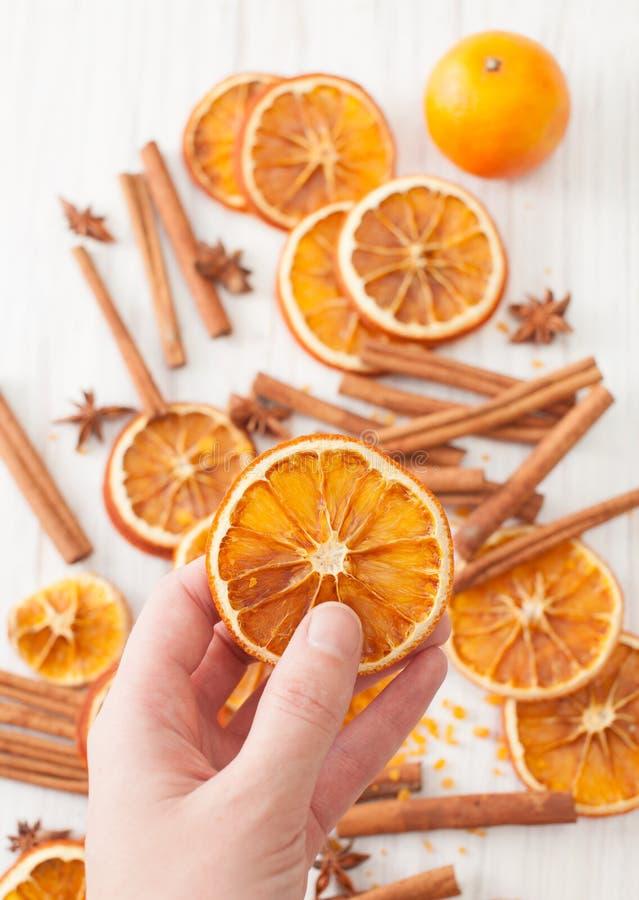Un círculo de la naranja secada en su mano contra otra imagen de archivo