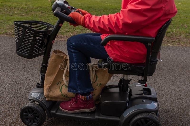 Un côté sur le tir d'une dame pluse âgé dans un manteau rouge appréciant la liberté d'un scooter électrique de mobilité photo stock