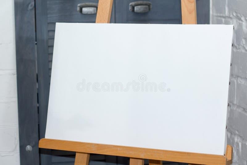 Un caballete con una lona blanca limpia está listo para el trabajo contra una pared de ladrillo, un fondo o un concepto blanco imagen de archivo