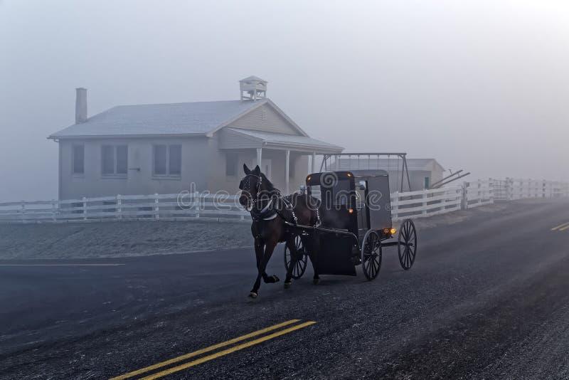 Un caballo y un carro pasa una casa de la escuela de Amish imágenes de archivo libres de regalías