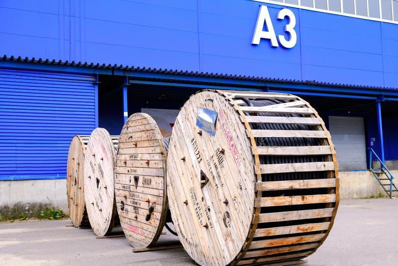 Un cable eléctrico grueso sobre cucharas de madera Las bobinas están marcadas Almacén Terminal de almacenamiento, edificio azul foto de archivo