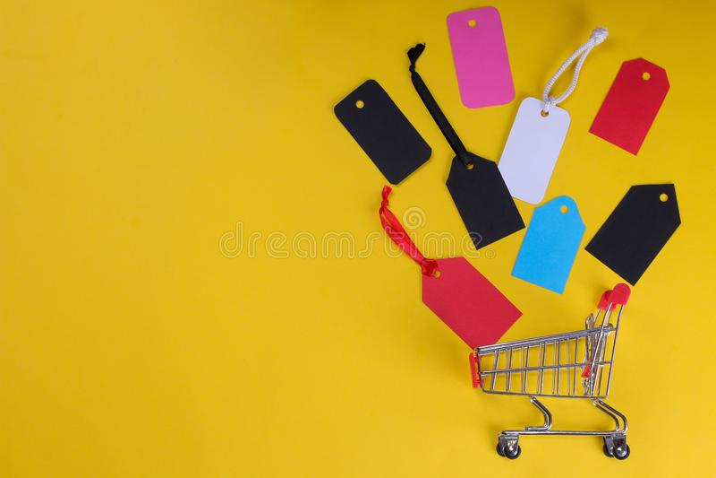 Un caddie avec les étiquettes et les prix à payer multicolores sur un fond jaune lumineux d'un concept noir de vendredi Achats Vu photos stock