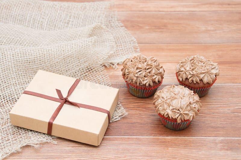 Un cadeau en boîte et trois petits gâteaux photo stock