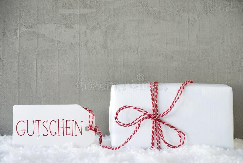Un cadeau, fond urbain de ciment, texte Gutschein signifie le bon images stock