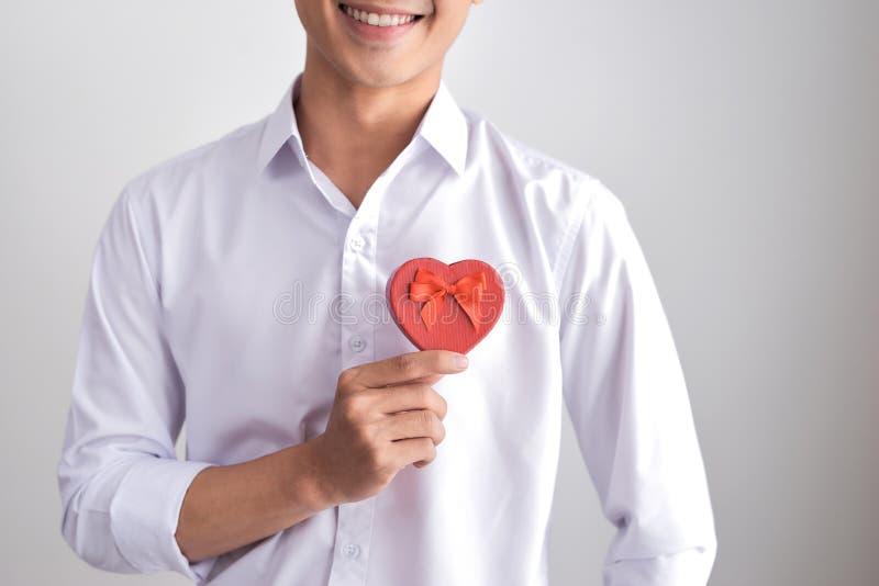 Un cadeau pour l'aimé Jeune bel homme élégant de sourire dans une chemise blanche tenant une boîte avec un cadeau et des expositi images libres de droits