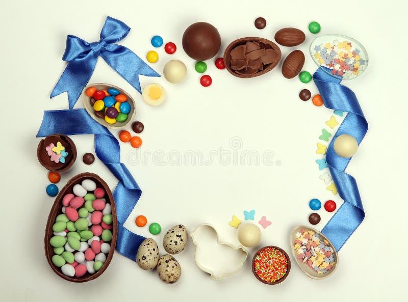 Un cadre des oeufs de pâques de chocolat, des bonbons des rubans et des arcs sur un fond blanc d'isolement images stock
