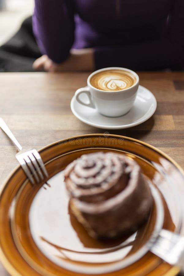 Un café con leche plano con un bollo de canela del hacia fuera-de-foco en el primero plano imagenes de archivo