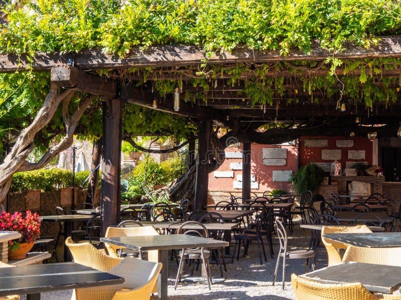 Un café confortable sous un auvent vert animé sur les banques de la rivière Aniene dans Tivoli, Italie images stock