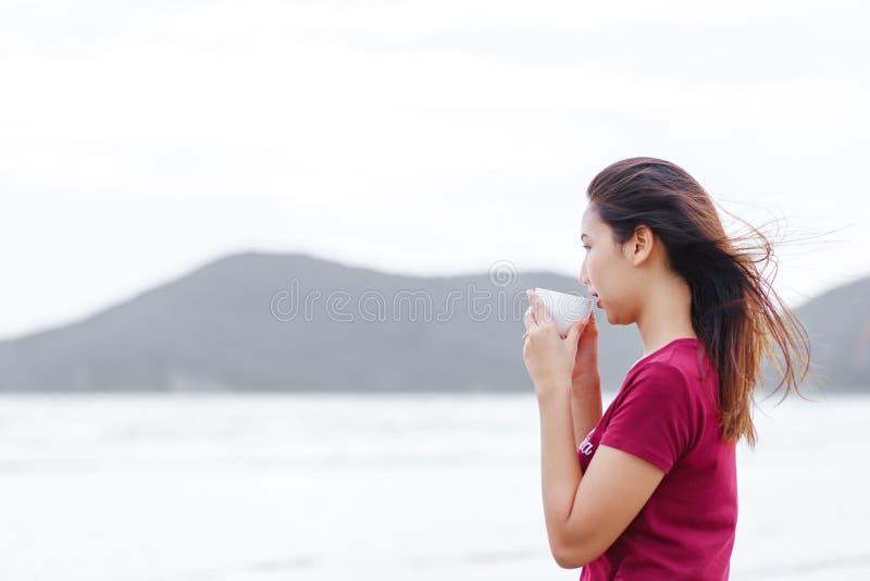 Un café de boissons de femmes près de la plage elle se tiennent sur la plage et utilisent la chemise rouge images stock