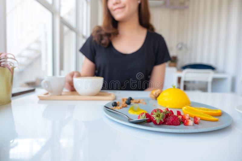 Un café de consumición de la mujer asiática hermosa y consumición de la torta anaranjada con la fruta mezclada imagen de archivo libre de regalías