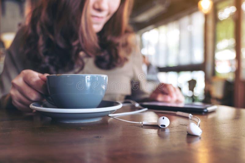 Un café de consumición de la mujer mientras que escucha la música con el teléfono móvil y el auricular imágenes de archivo libres de regalías