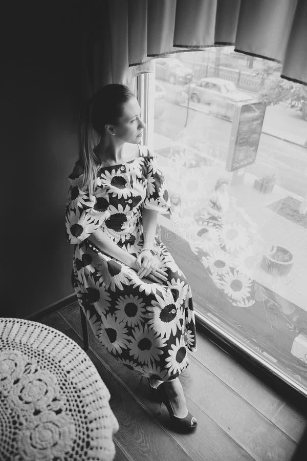 Un café Mujer en el café que piensa mirando hacia fuera la ventana Modelo caucásico hermoso joven en un vestido largo imagen de archivo libre de regalías
