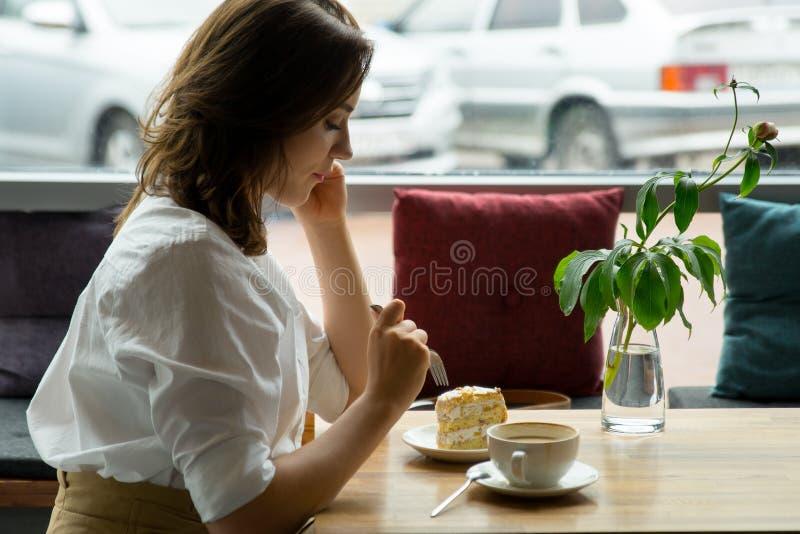 Un café potable de jeune belle femme dans un café la jeune femme dans les affaires vêtx sur une pause de midi photographie stock libre de droits