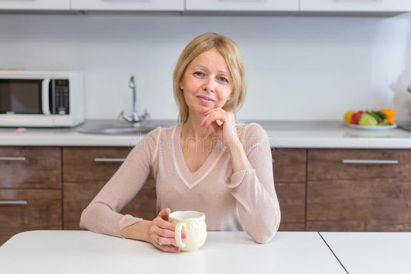Un caffè bevente della donna senior attiva a casa fotografia stock