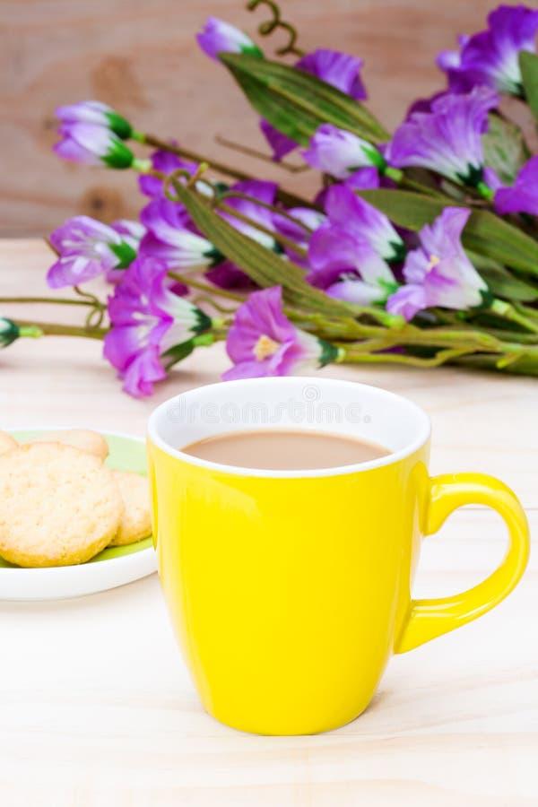Un caffè caldo in tazza di yello e biscotto di burro su legno fotografia stock