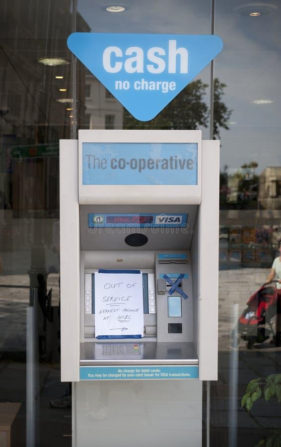 Un cajero automático del banco cooperativo con una muestra fuera de servicio en la calle principal en la ciudad de St Pierre Port imagen de archivo libre de regalías