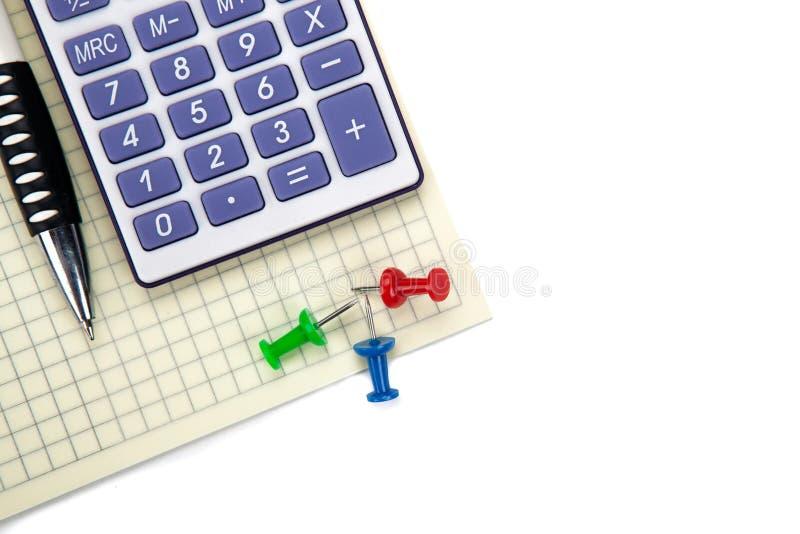 Un calculadora y efectos de escritorio grandes en una tabla blanca imagenes de archivo