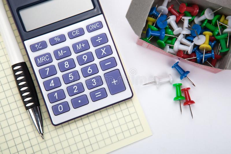 Un calculadora y efectos de escritorio grandes en una tabla blanca imagen de archivo
